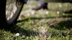 Steering with a motorbike wheel motionless and leaving from a flowered grass. Stock Footage