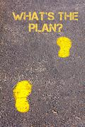Yellow footsteps on sidewalk towards Whats The Plan message.Concept image Stock Photos