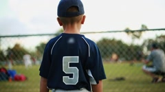 Little kid in baseball uniform watching practice behind fence at field - stock footage