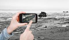 Tourist taking photo tracked vehicle on ice road Stock Photos