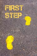 Yellow footsteps on sidewalk towards First Step message.Concept image Stock Photos