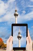 tourist taking photo of TV tower on alexanderplatz - stock photo