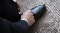 Man in suit tying shoelaces before going to work Stock Footage
