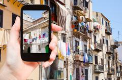 tourist taking photo of municipal house in Palermo - stock photo