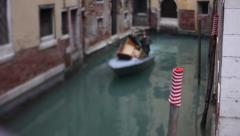 Boat sailing in a venetian canal near a wooden stake with a striped sock on it. Stock Footage