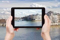 tourist taking photo of Pont Louis-Philippe - stock photo