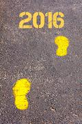 Yellow footsteps on sidewalk towards 2016 message.Concept image - stock photo