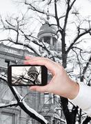 tourist taking photo of snow on bare tree - stock photo