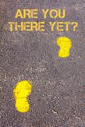 Yellow footsteps on sidewalk towards Are We There Yet message.Concept image Stock Photos