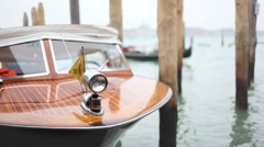 Berth taxi boat rocking in the venetian lagoon while a gondola passing. - stock footage