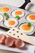 Six fried eggs in an old pan Stock Photos
