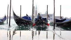 Dock gondolas rocking on venetian lagoon in a cloudy day. Stock Footage