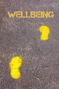 Yellow footsteps on sidewalk towards Wellbeing message.Concept image - stock photo