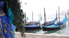 Blue and green carnival mask nearby venetian lagoon and gondolas fluttering. Stock Footage
