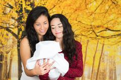 Portrait of beautiful lesbian couple holding their baby Stock Photos