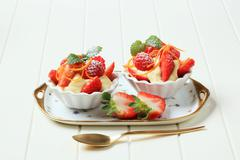 Creamy pudding and fresh fruit in small dessert dishes - stock photo
