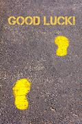 Yellow footsteps on sidewalk towards Good Luck message.Concept image Stock Photos