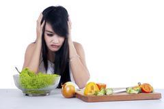 Woman hesitate to eat salad 1 Stock Photos
