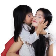Young girl kiss her mom in studio Stock Photos