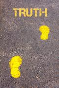 Yellow footsteps on sidewalk towards Truth message.Concept image Stock Photos