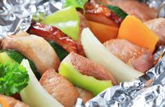Pork and vegetable skewers in aluminum foil - stock photo
