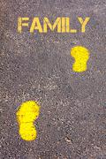 Yellow footsteps on sidewalk towards Family message.Conceptual image Stock Photos