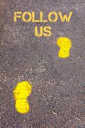 Yellow footsteps on sidewalk towards Follow Us message.Conceptual image - stock photo