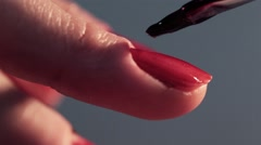 Woman doing a manicure cosmetic beauty treatment. Brush causes red lacquer Stock Footage