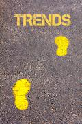 Yellow footsteps on sidewalk towards Trends message.Conceptual image Stock Photos