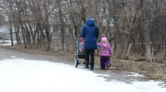 Mother with Daughter Walkin in Park with Newborn Child in  Baby Carriage Stock Footage