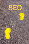 Yellow footsteps on sidewalk towards SEO message.Conceptual image Stock Photos