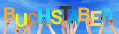 People Holding Colorful German Word Buchstaben Means Letters Blue Sky - stock photo