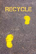 Yellow footsteps on sidewalk towards Recycle message.Conceptual image Stock Photos