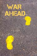 Yellow footsteps on sidewalk.War Ahead message.Conceptual image Stock Photos