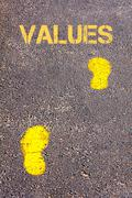 Yellow footsteps on sidewalk.Values message.Concept image - stock photo