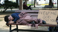 Homeless, sick child lying on bench Stock Footage
