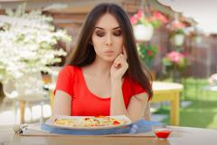 Young Woman Thinking About Eating Pizza on a Diet - stock photo