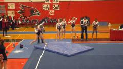 College gymnast misses landing on tumbling routine (falls off mat) Stock Footage