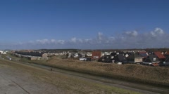 Dutch village behind sea dike + pan roofs of houses below sea level Stock Footage