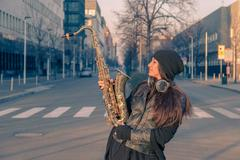 Beautiful young woman with her saxophone Stock Photos