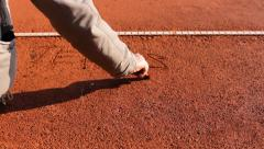 Write TENNIS on Red clay tennis court Stock Footage