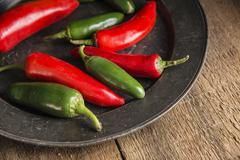Red and green peppers in vintage retro moody natural lighting setting Stock Photos