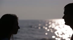 silhouette of a loving couple. Kiss of the sea. slow motion - stock footage
