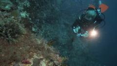 Scuba diver filming along coral reef wall using led lights Stock Footage