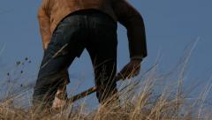 man in jeans and jacket dig with a spade - stock footage