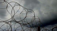 Barbed wire  trembling in the wind on the  dark stormy clouds background. Stock Footage