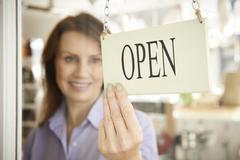 Store Owner Turning Open Sign In Shop Doorway Stock Photos