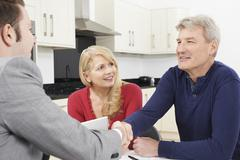 Mature Couple Shaking Hands With Financial Advisor At Home Stock Photos