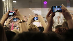 Stock Video Footage of Many viewers are shooting a fashion show on a mobile device.