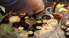 Lots of chocolates on display. Pastry chef lays out the candy on the storefront. - stock footage